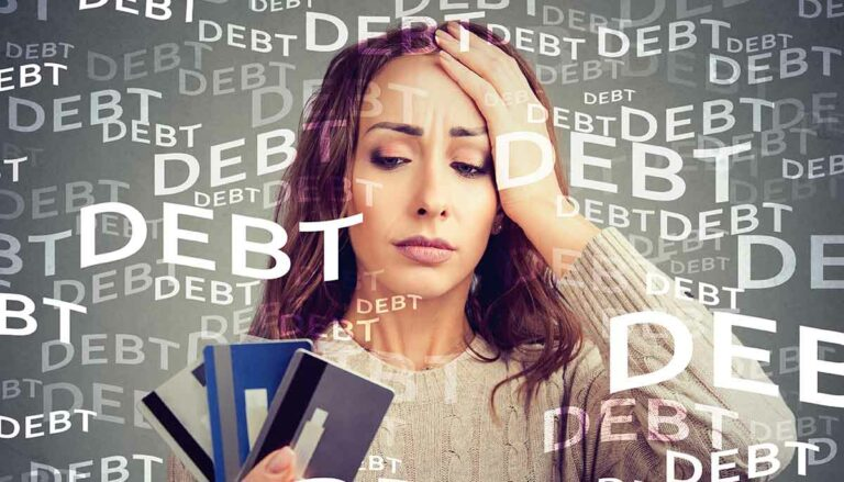 a concerned woman looks at credit cards she has accumulated a lot of debt on