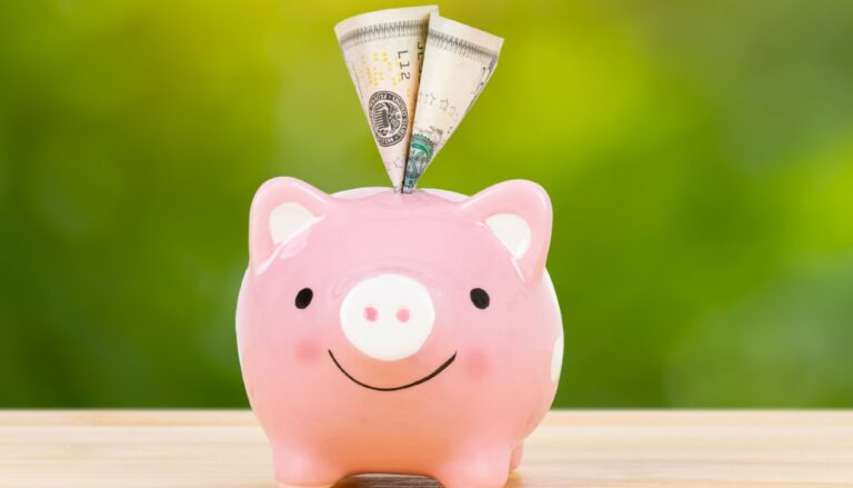 a happy pink piggy bank with money sticking out