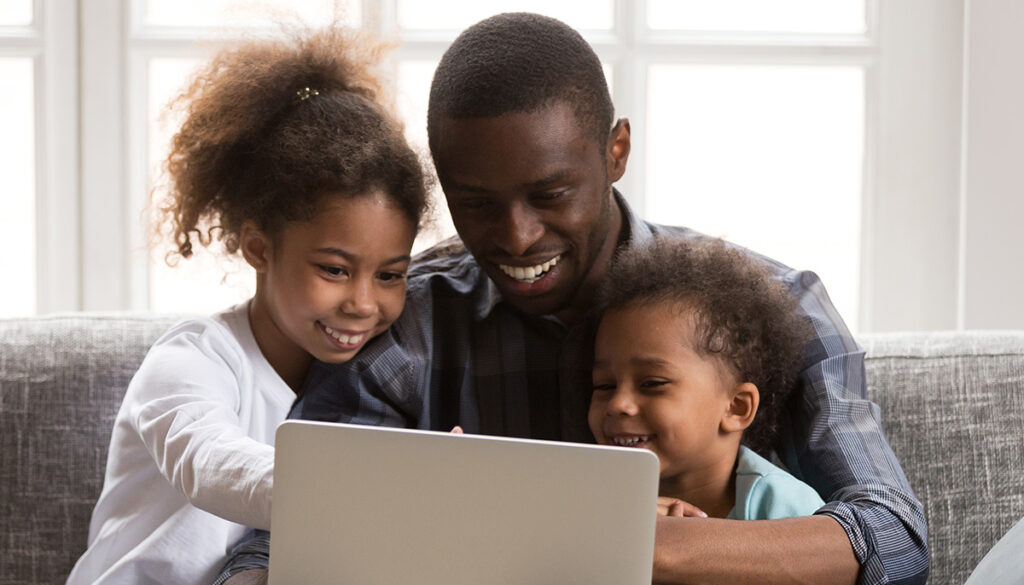 dad-daughter-and-son-sit-on-couch-and-laugh-at-laptop-screen